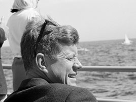 Photo of John F. Kennedy on a boat. Link to Gifts of Cash, Checks, and Credit Cards