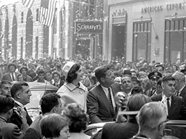 Photo of John F. and Jacqueline Kennedy riding through a parade. Link to Closely Held Business Stock